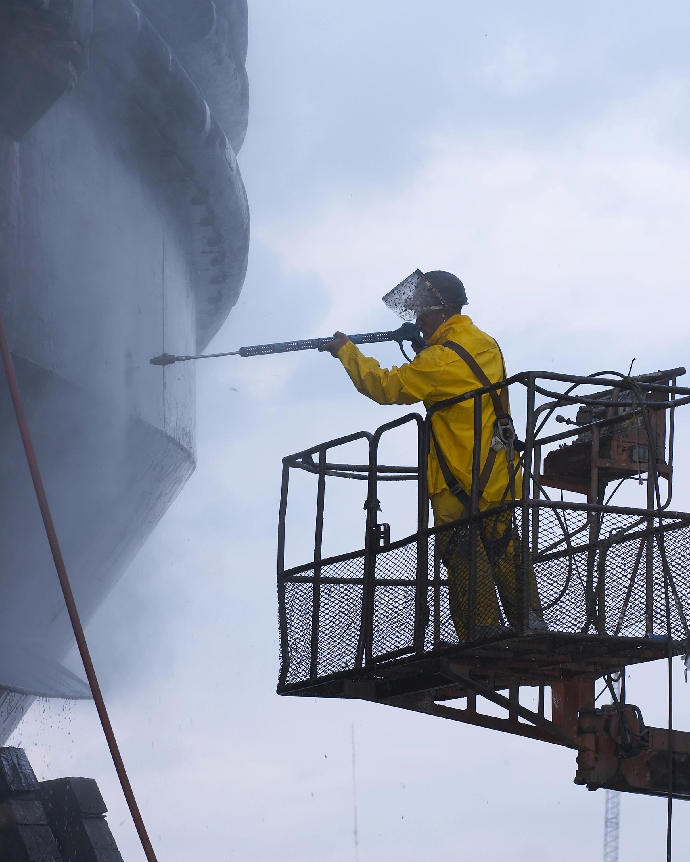 Homme sur une plateforme se servant d'un nettoyeur très haute pression