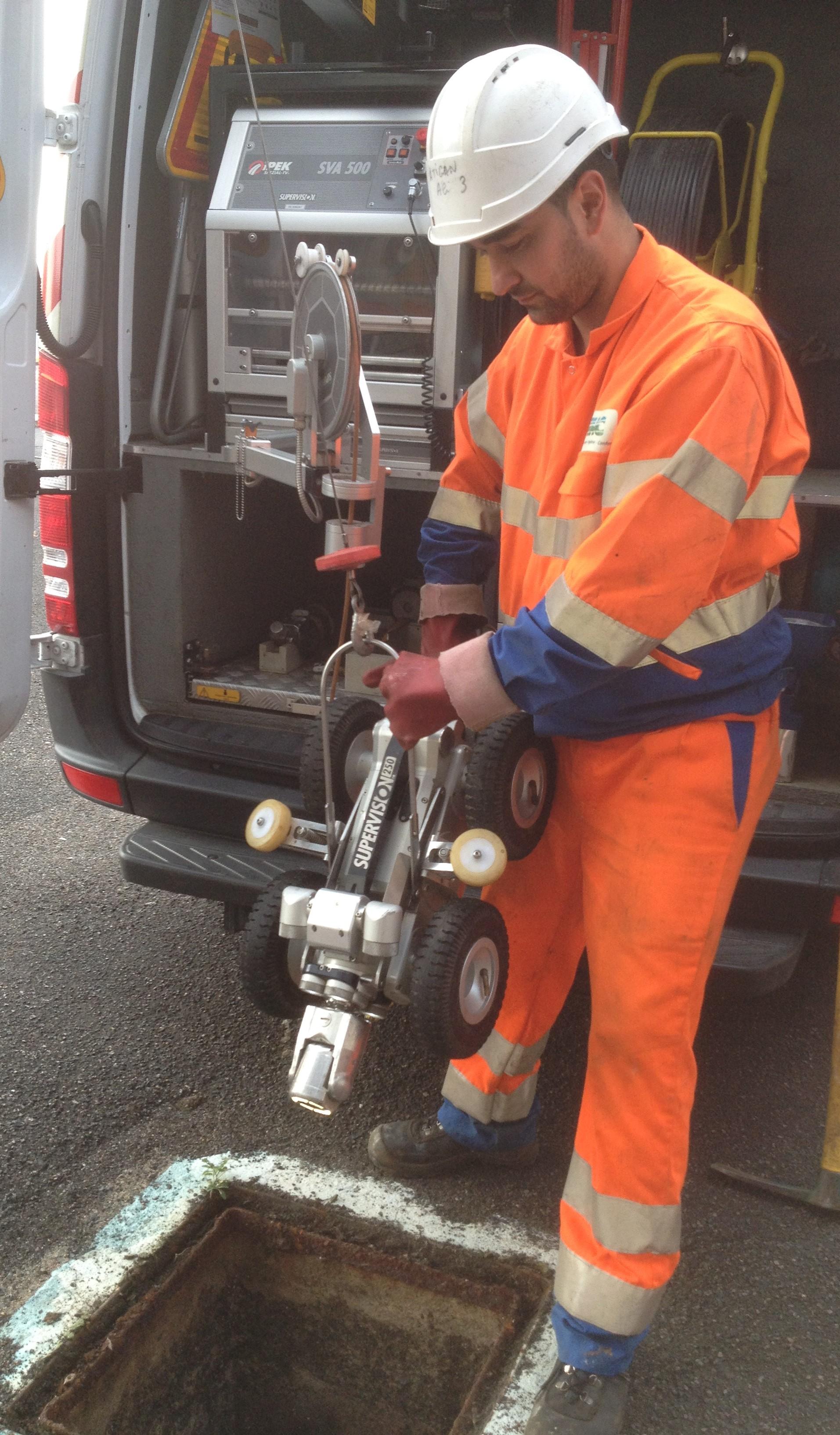 Technicien procédant à la descente d'un robot dans les canalisations pour une inspection télévisée